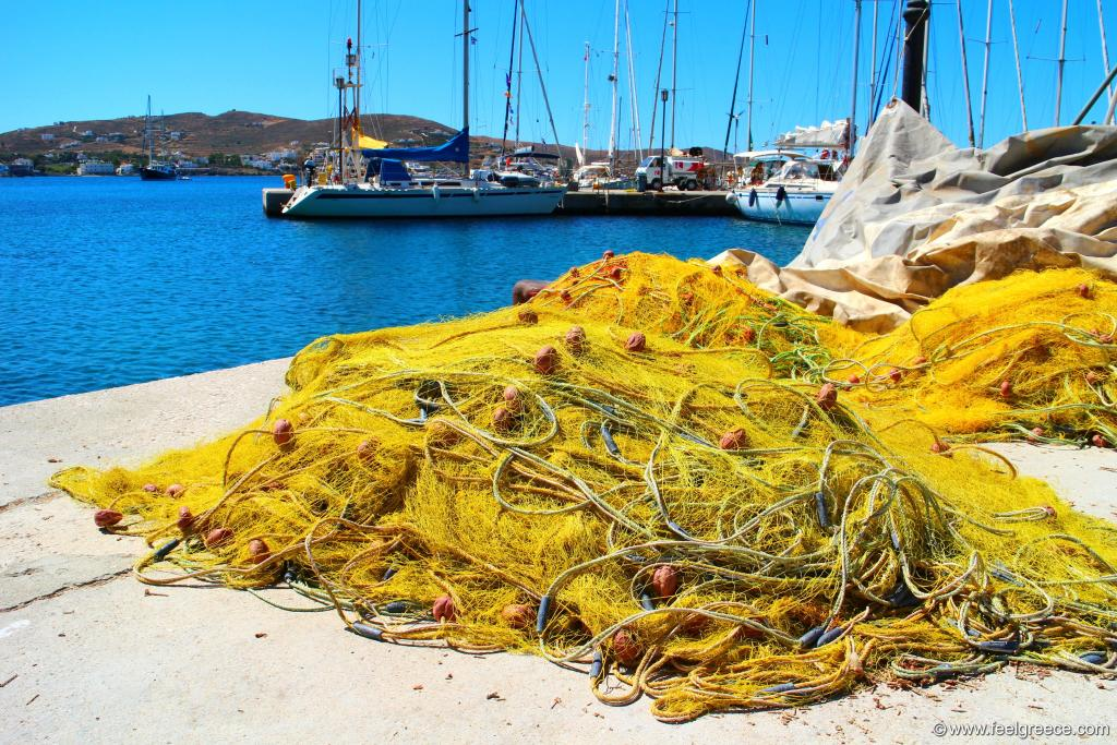 Piles of yellow fishing nets drying at the sun
